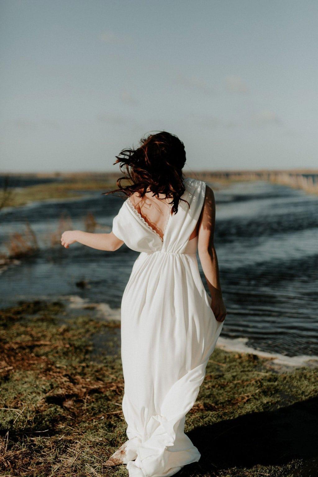 Robe de mariée bohème en crêpe drapé, décolleté au dos et agrémentée d'un galon de dentelle fleurie