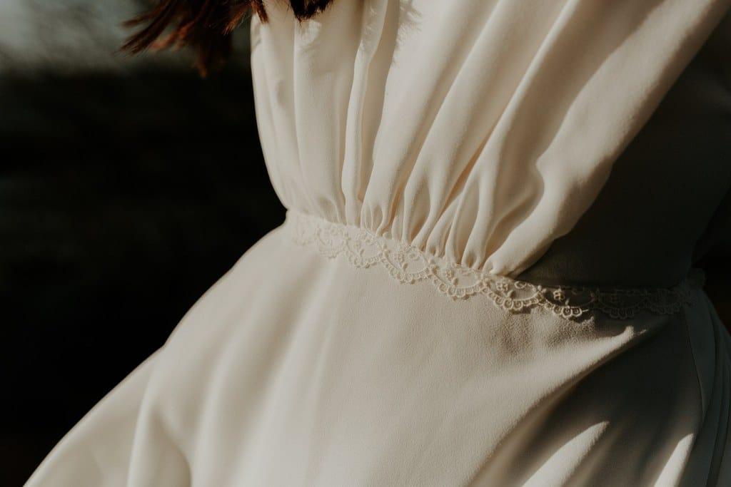 Détails robe de mariée en crêpe drapée avec galon de dentelle fleurie à la taille