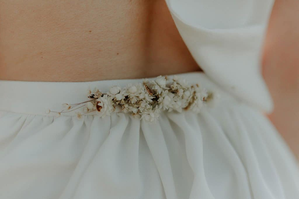 Détails dos robe de mariée en crêpe avec broche amovible en fleurs séchées et stabilisées
